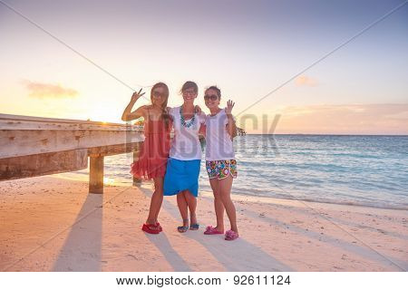 group of friends on beautiful beach at sunset going back to home