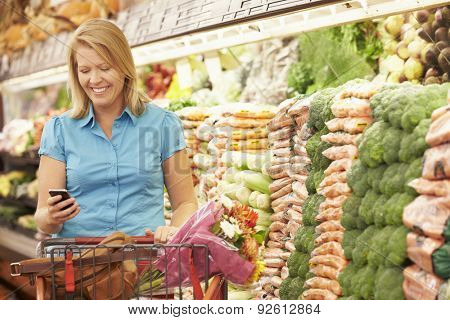 Woman Using Mobile Phone In Supermarket