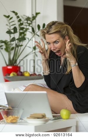 Young hysterical blonde woman screaming at laptop. Stressed woman.