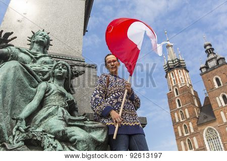 Young woman with the flag of the Republic of Poland on the main square of Krakow, St. Mary's Church in the background.