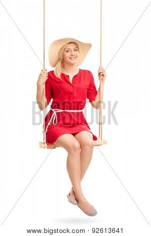 Beautiful woman in a red dress and a stylish hat swinging on a wooden swing isolated on white background