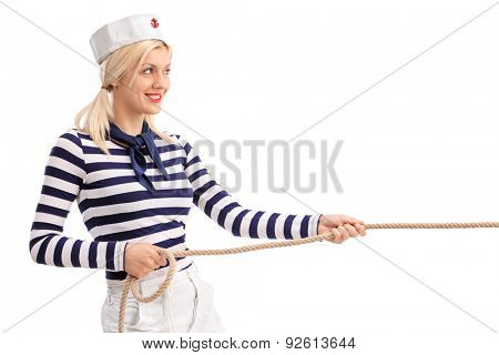 Cheerful female sailor pulling a rope and smiling isolated on white background