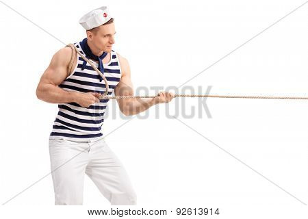 Studio shot of a young man in sailor uniform pulling a rope isolated on white background