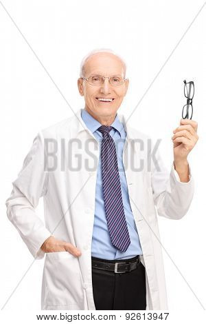 Vertical shot of an experienced mature optician holding a pair of glasses and looking at the camera isolated on white background
