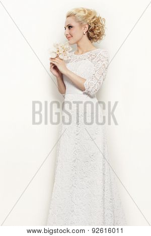 Young slim beautiful blonde happy smiling bride in lacy dress over white wall