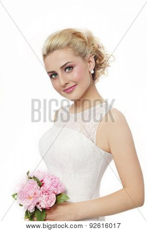 Young beautiful blonde happy smiling bride in lacy dress, with bouquet over white background