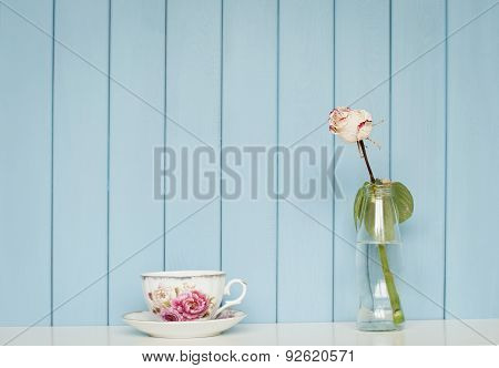 Cup Of Tea And White Rose In The Bottle