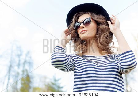 bright beautiful young happy girl in hat and sun glasses walking in the park on a sunny day