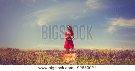 Girl In Red Dress With Suitcase And Camera On The Meadow