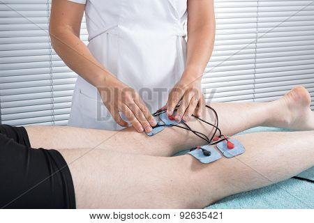 Man With Electrostimulator Electrodes On His Legs