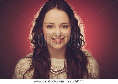 Beauty portrait of young modest brunette woman smiling on red background.