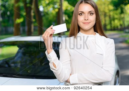 Young woman standing near car and showing card