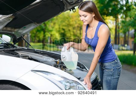 Pretty girl pouring liquid for car