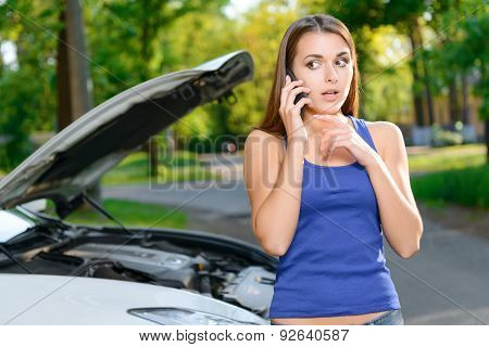 Pretty confused girl talking per mobile phone