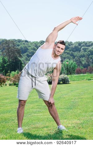 Handsome sportsman doing exercises outdoors