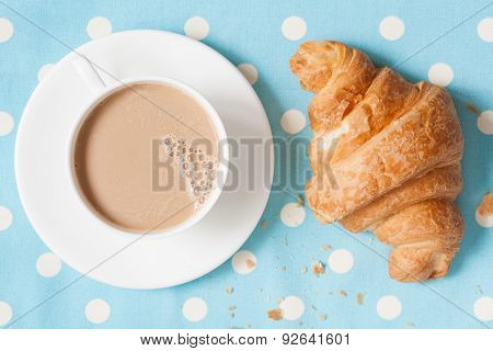 Cup of coffee latte and croisssant, traditional French viennoiserie dessert on provence style backgr
