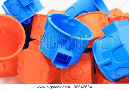 Heap Of Orange And Blue Electrical Boxes On White Background