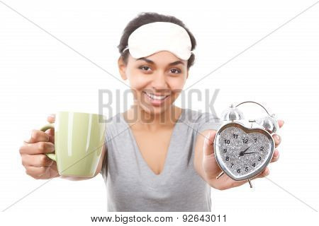 Smiling mulatto girl showing cup and alarm clock