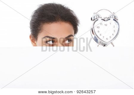 Pleasant woman fixedly looking at alarm clock