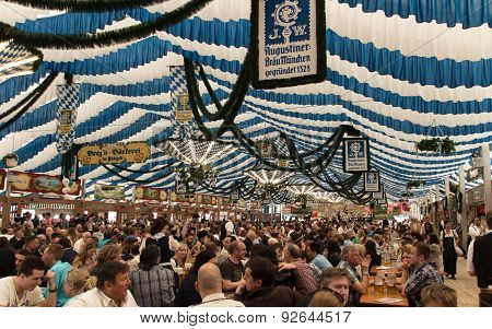 Munich, Germany - April 26, 2015: Traditional dressed people with dirndls and leather trousers in a beer tent on Theresienwiese celebrating with beer and music