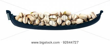Fresh Salted Pistachios in boat. Isolated on white background