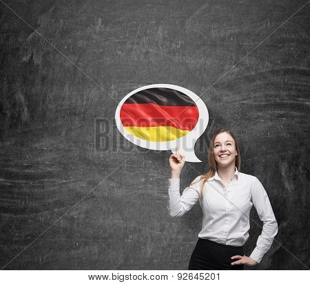 Beautiful Woman Is Pointing Out The Thought Bubble With German Flag. Dark Background.