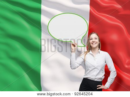 Woman Is Pointing Out The Blank Speech Bubble. Italian Flag As A Background.