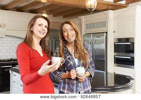 Mature Female Friends Standing In New Luxury Fitted Kitchen