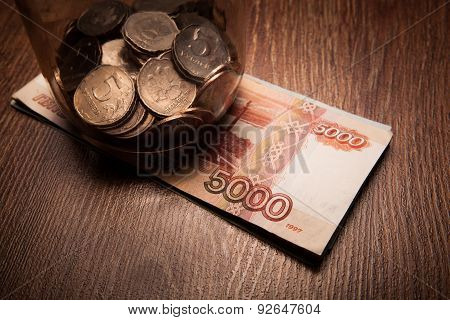 Bundle Of Bank Notes And A Glass Jar With Coins