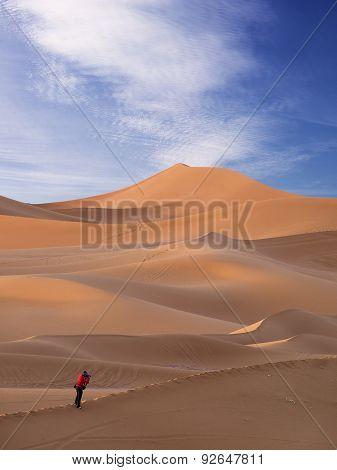 Woman Traveler  Looking Through Camera In Sahara Desert