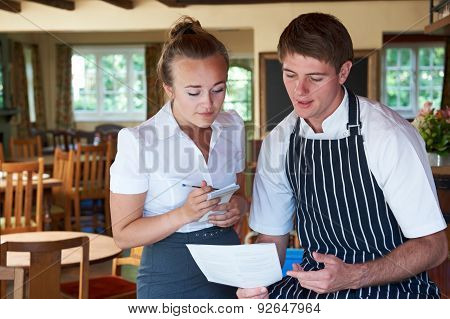 Chef And Waitress Discussing Menu In Restaurant