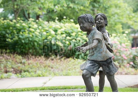 Lifesize, bronze statues of a young boy and girl playing tag