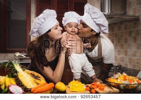 Attractive Mixed Race Young family with baby cooking dinner