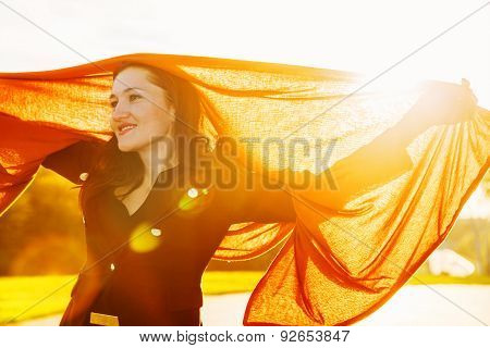 Happy Woman With Long Brown Fluttering Scarf On Sunset