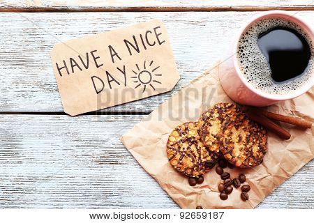 Cup of coffee with fresh cookies and Have A Nice Day massage on wooden table, top view