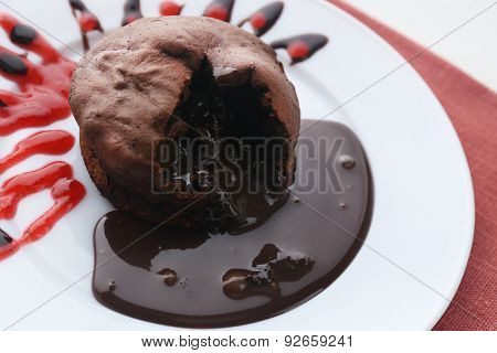 Chocolate fondant with strawberry cream on white plate, closeup