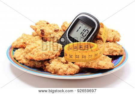 Glucometer, Oatmeal Cookies And Tape Measure On Colorful Plate