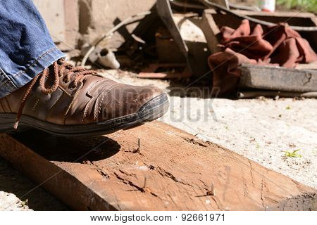 Worker steps on nail outdoors