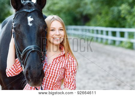 Smiling girl taking care of the horse