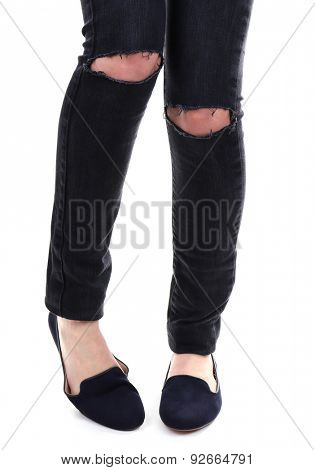 Woman in torn jeans on knees and shoes isolated on white