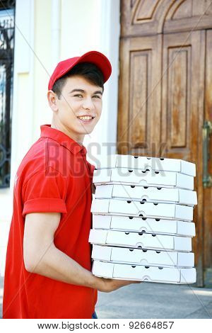 Young man delivering pizza box near house