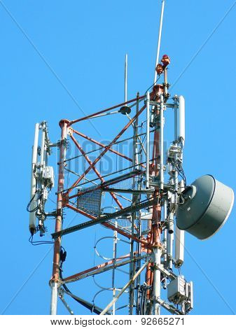 Communication Tower with Parabolic and GSM Antennas LTE and Blue Sky close up