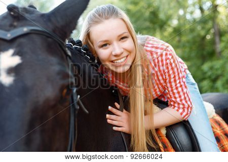 Young girl lying on the horse
