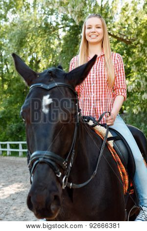 Upbeat girl riding the horse
