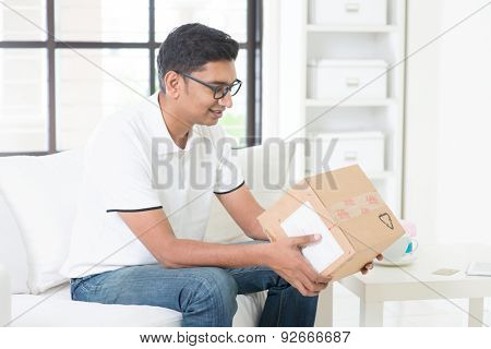 Courier delivery concept. Indian guy received an express parcel and checking the box at home.