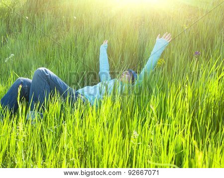 Young Girl Resting On The Grass.