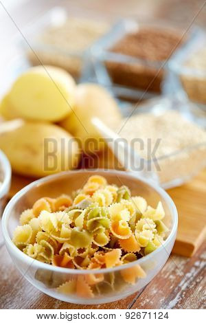 diet, cooking, culinary and carbohydrate food concept - close up of pasta and other foodstuffs in glass bowls on table