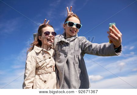 people, children, technology, friends and friendship concept - happy girls with smartphone taking selfie and making funny faces outdoors