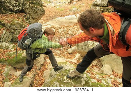 Man giving helping hand to friend to climb mountain rock cliff.