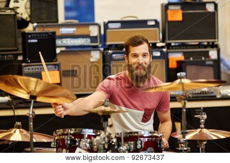music, sale, people, musical instruments and entertainment concept - male musician playing cymbals on drum kit at music store